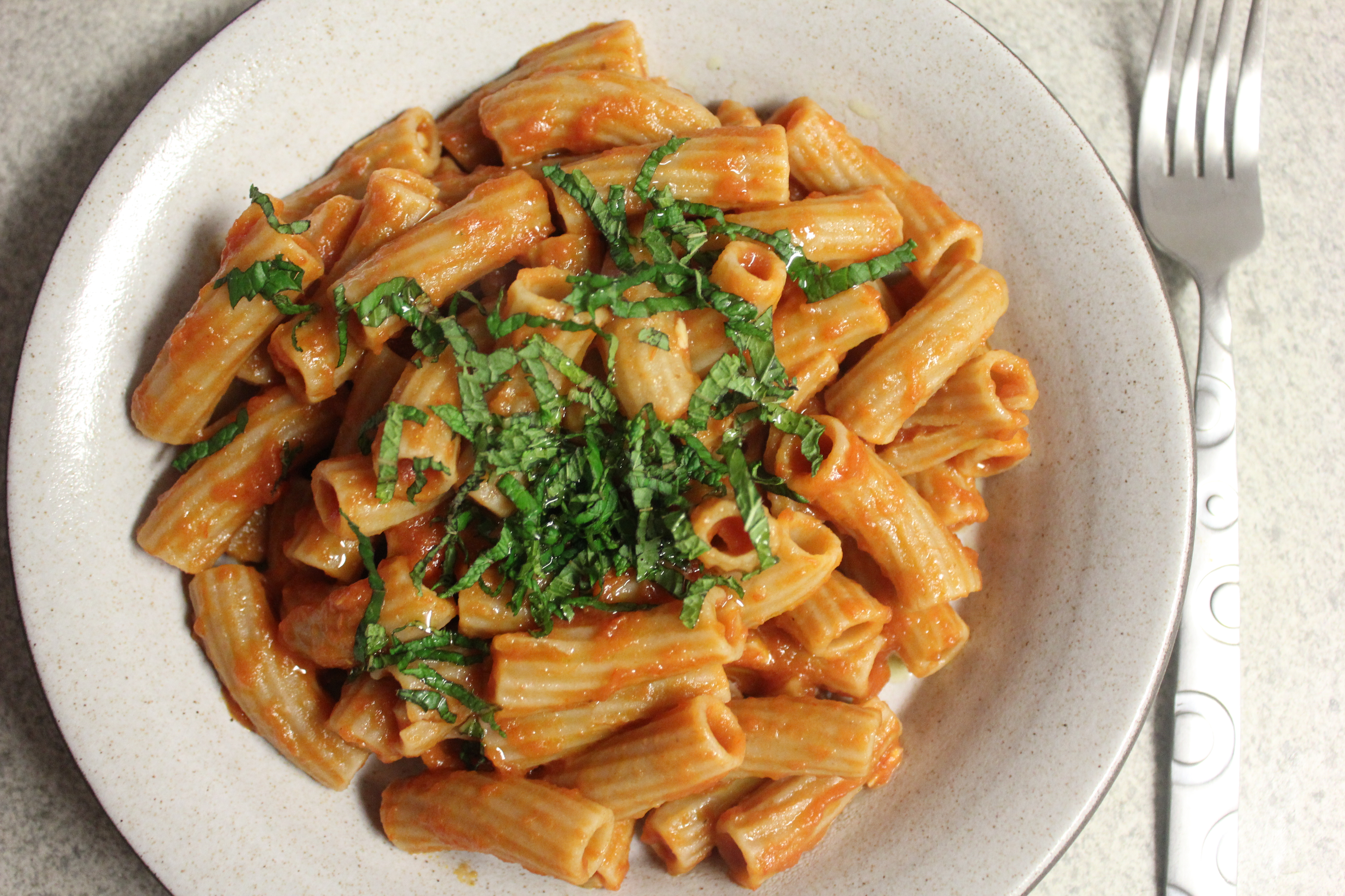 A plate of pasta with tomato sauce made using flavored olive oil