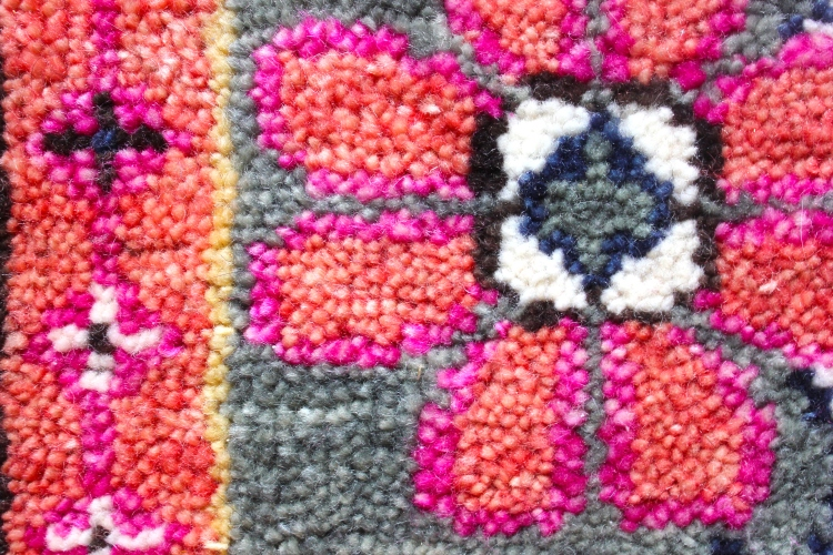 Close-up of a flower decoration on a colorful Persian Kismet rug by Caitlin Wilson.