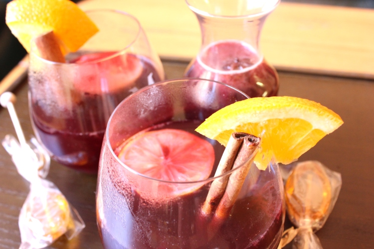 Mulled Wine for two with honey spoons, orange wedges, and cinnamon sticks.