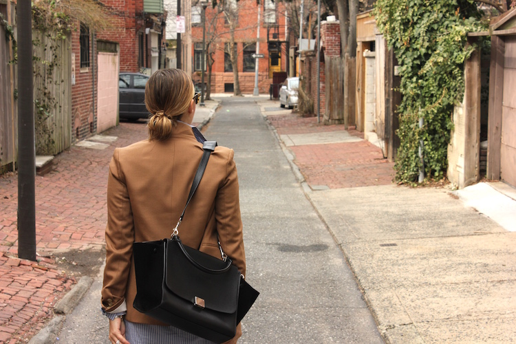 Back view of Allie wearing a blazer and a slung-back bag in a silent alley on a Philadelphia morning