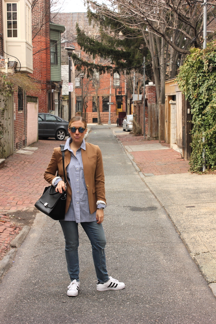 Allie standing in an alley in Philadelphia, wearing a blazer, sneakers, and a Celine bag
