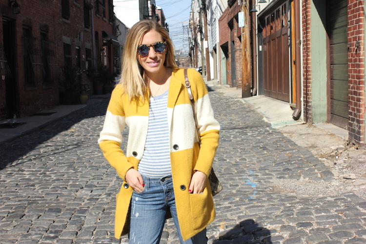 Allie with a striped t-shirt, a mustard cardigan, and jeans