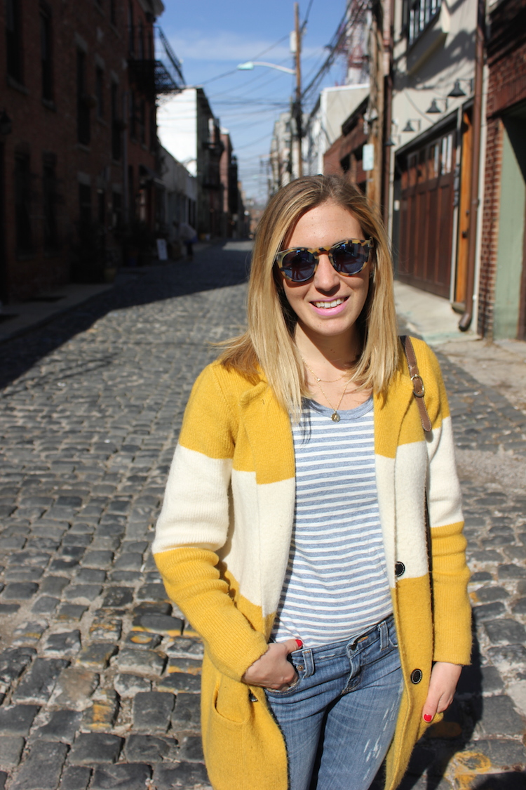 Allie lounging in a cobblestone alley with leopard sunglasses on a warm day