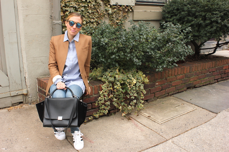 Sitting in front of ivy in Philadelphia, wearing sunglasses, a blazer, an