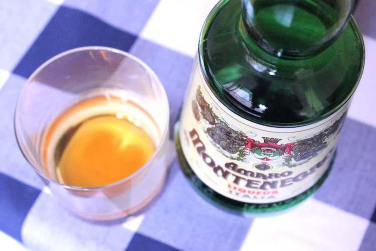 A glass and bottle of Amaro Montenegro, a popular Italian amaro drink