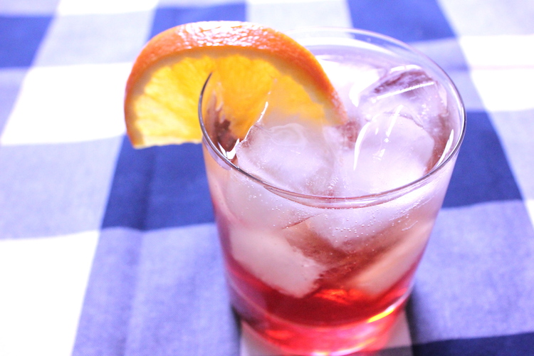 An Americano Cocktail with an orange wedge for garnish