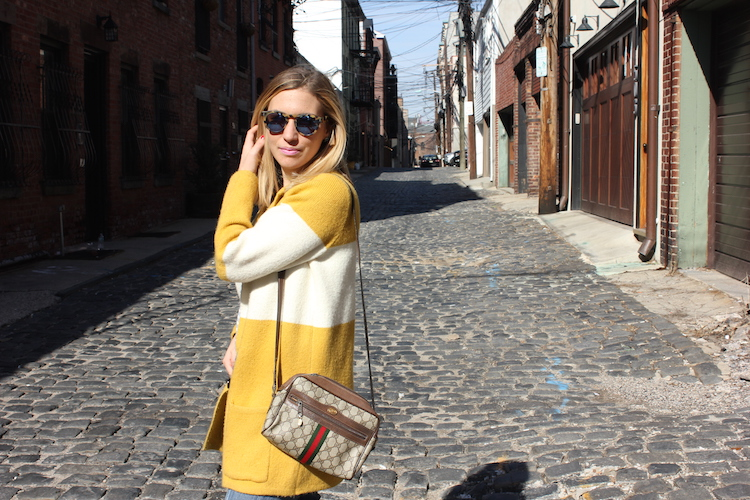 Showing off a yellow cardigan and vintage Gucci bag on a beautiful day