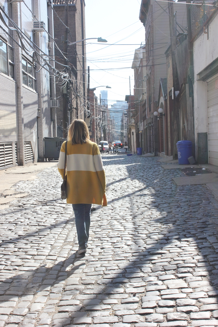 Allie walking down Court Street in Hoboken wearing a mustard cardigan from Anthropologie
