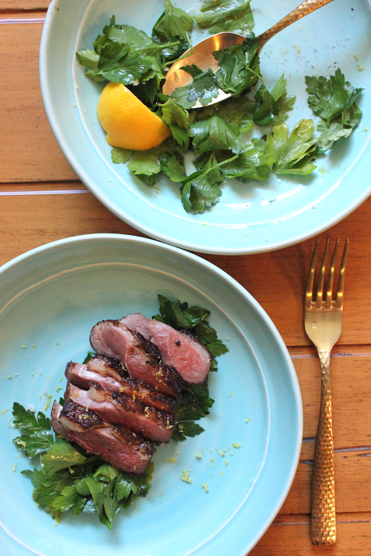 A plate of pan-sauteed duck breast and a plate of parsley salad