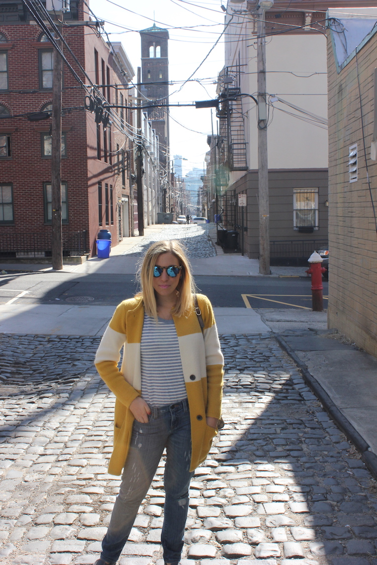Portrait shot in a Hoboken alley with a church tower in the distance
