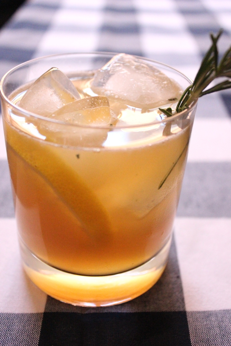 A maple bourbon sour with a rosemary sprig and lemon slice.