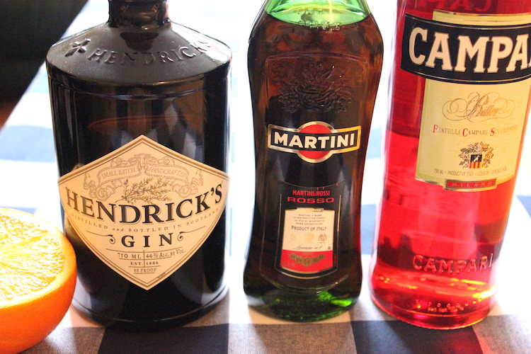 The ingredients for a negroni cocktail: campari, gin, and vermouth