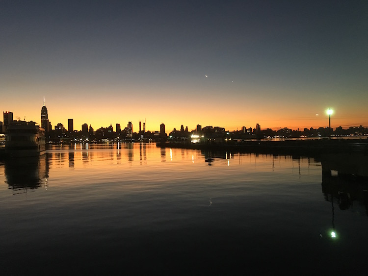 A flaming yellow glow behind the New York skyline as night turns to day