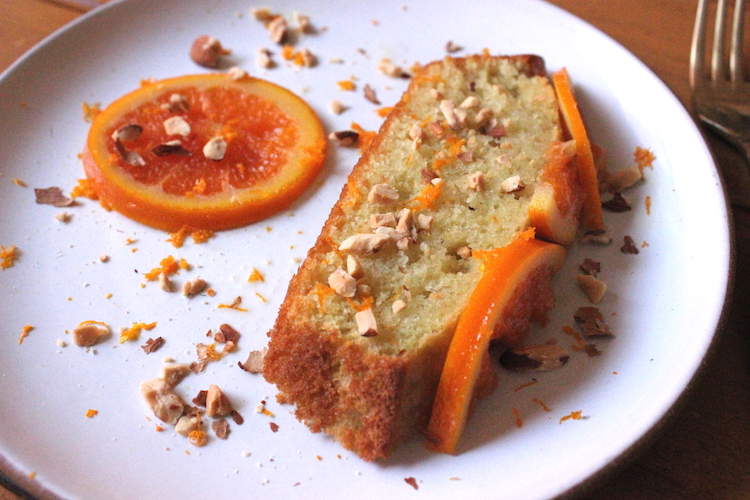 A plate of orange olive oil cake garnished with almonds and orange zest