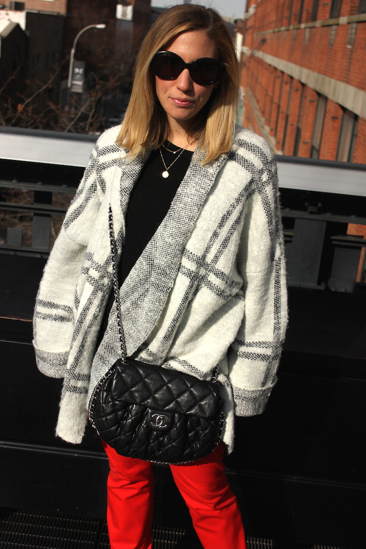 Person wearing an oversize sweater and black leather bag
