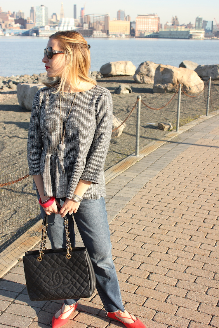 Allie wearing a peplum shirt and jeans on the Hoboken waterfront
