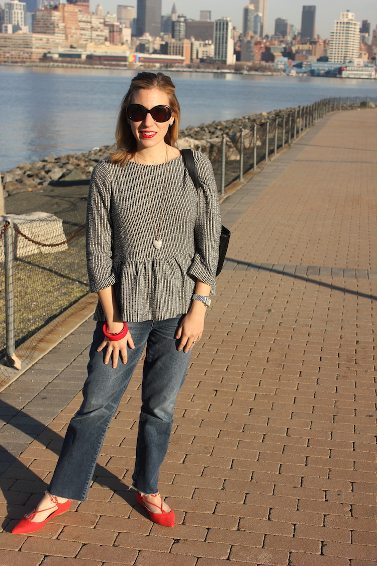 Allie wearing a peplum shirt and sunglasses on the Hoboken waterfront