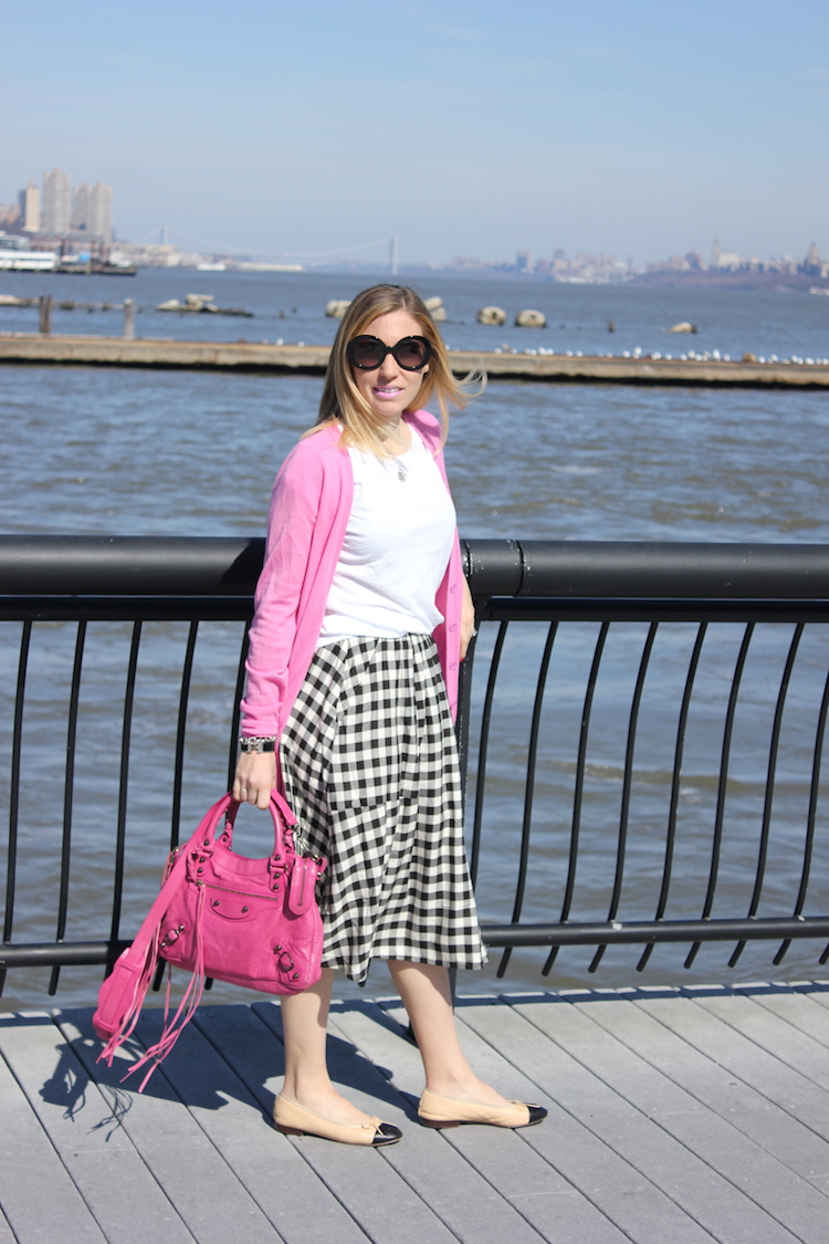 Wearing a pink JCrew Cardigan and a pink bag on the Hoboken waterfront