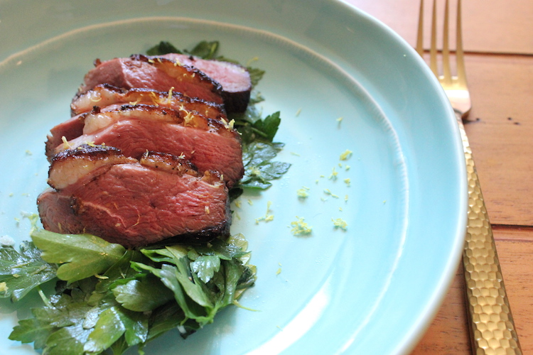Slices of cooked duck over unchopped parsley gremolata