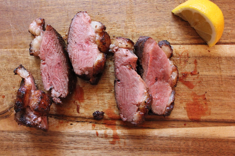 Just-sliced duck breast on a cutting board