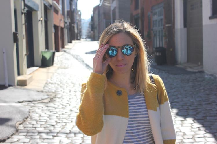 Adjusting leopard Illesteva sunglasses during a fashion shoot