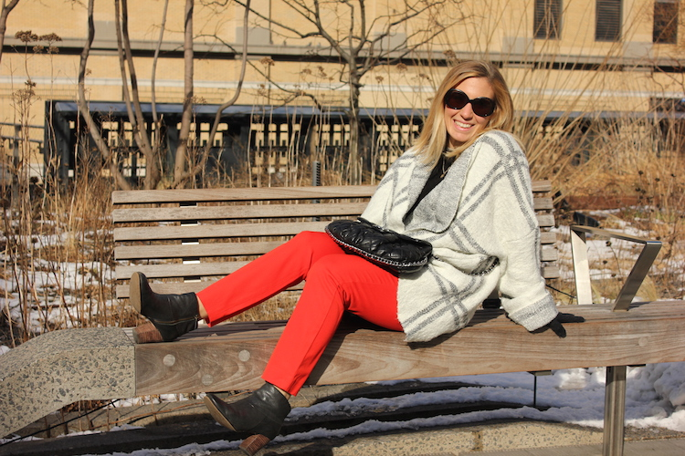 Allie wearing red pants and an oversize sweater on a bench in New York