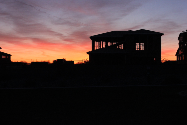A house under construction in silhouette against an Arizona sunset