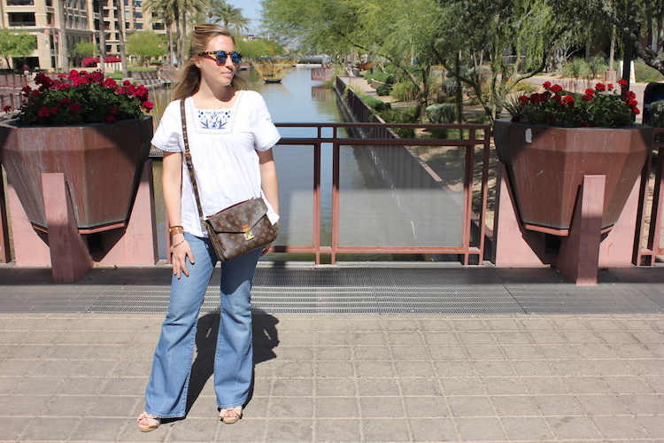 Allie in a blue and white embroidered shirt and 1970s style wide-bottom flare jeans