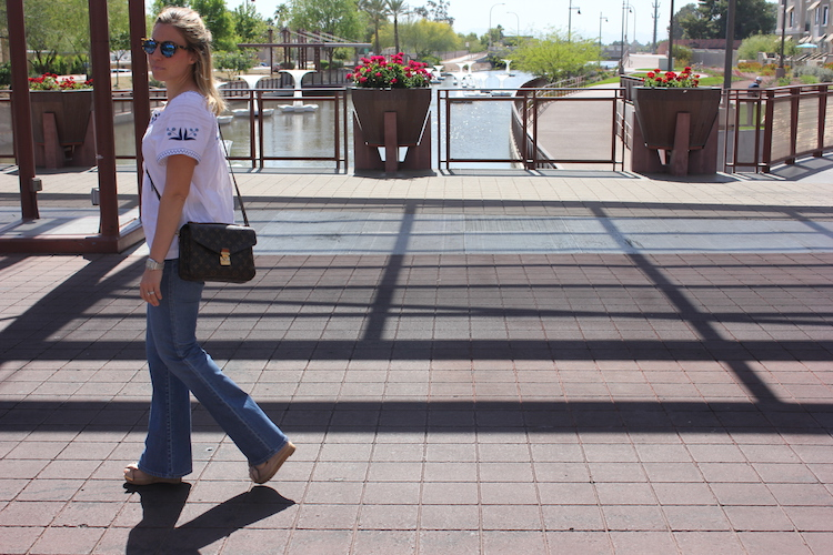 Allie walking with an embroidered shirt and denim flares