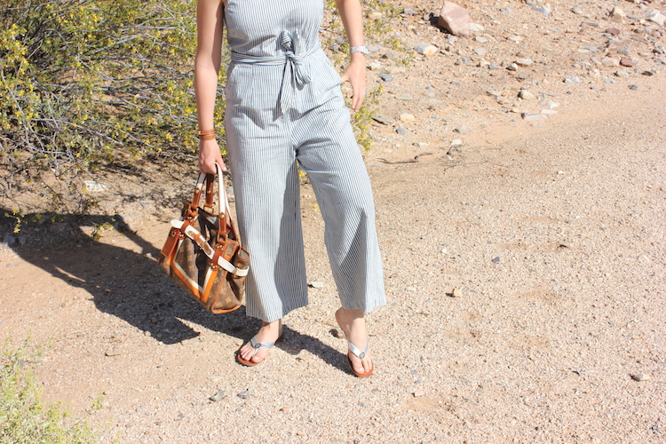 The bottom half of a summer jumpsuit, a bag, and sandals