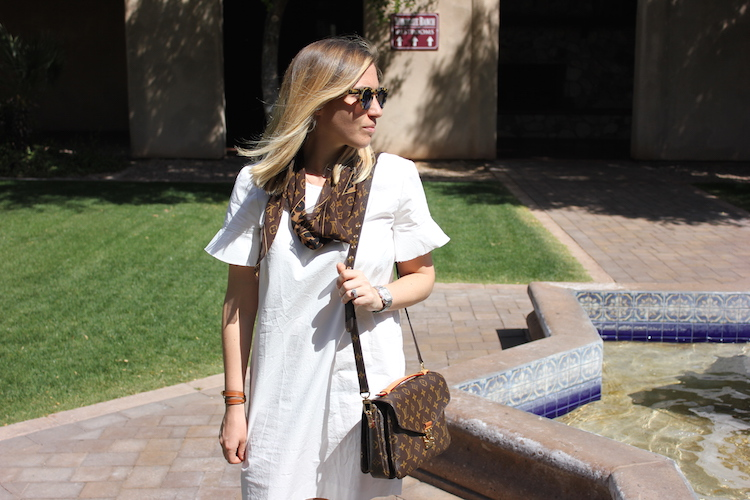 At the pool and wearing a white dress, a Louis Vuitton scarf, and a Louis Vuitton bag