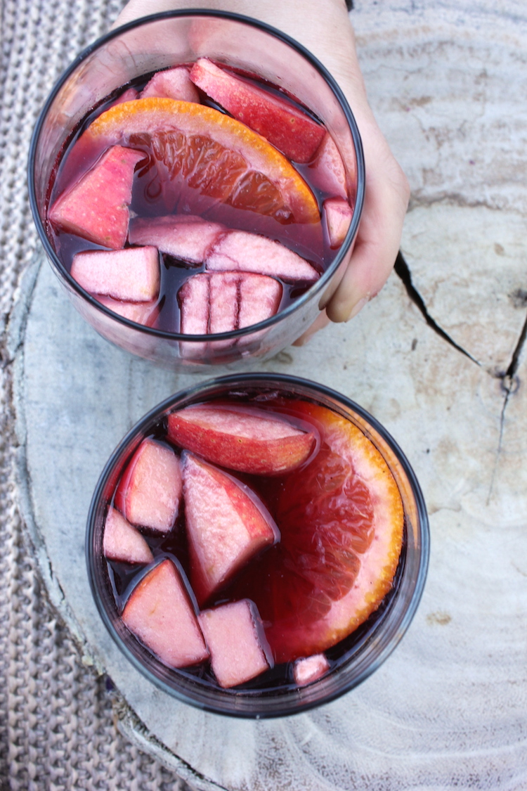 Two glasses of sangria with floating apple and orange slices